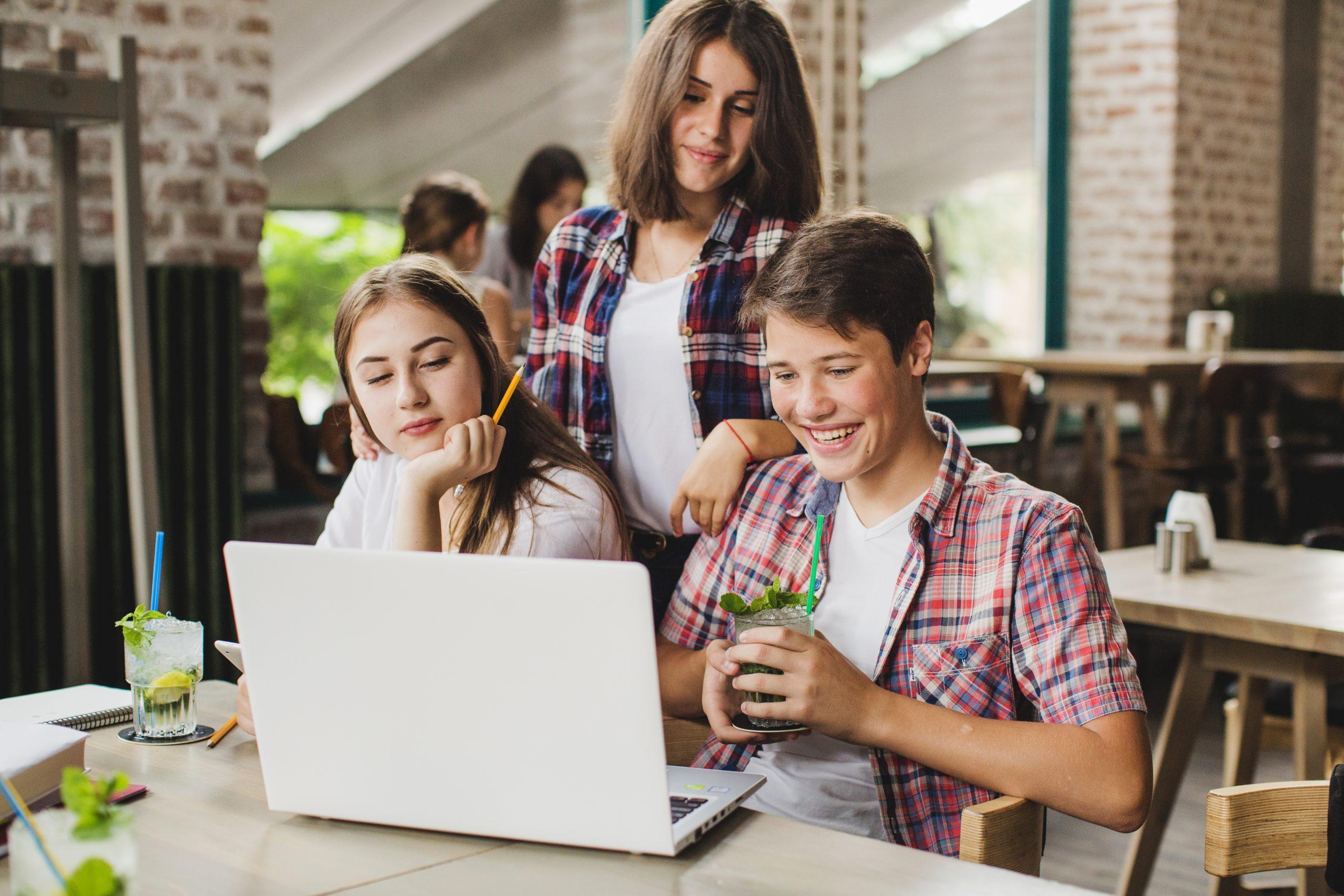 dwie nastolatki i nastolatek wpatrujący się w ekran komputera