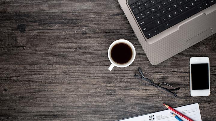 drewniany blat stołu, na którym znajdują się kubek z kawą, laptop, telefon, notes i okulary
