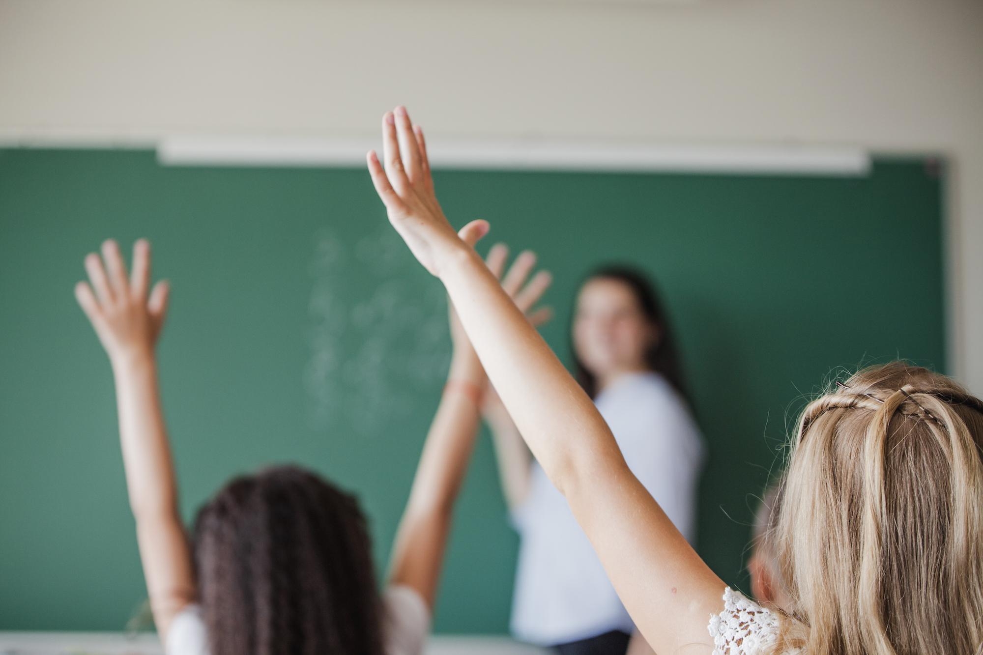 uczniowie podczas lekcji podnoszący ręce, aby zgłosić się do odpowiedzi