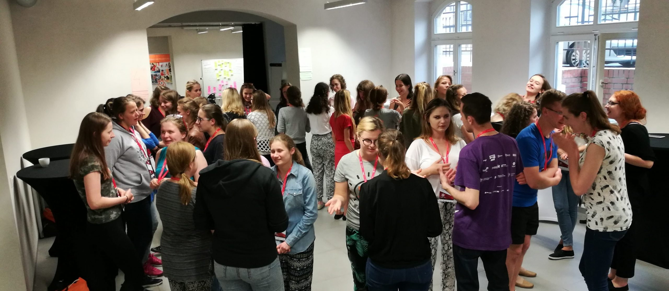 grupa kilkunastu młodych osób, które stoją w przestronnym pomieszczeniu i rozmawiają ze sobą