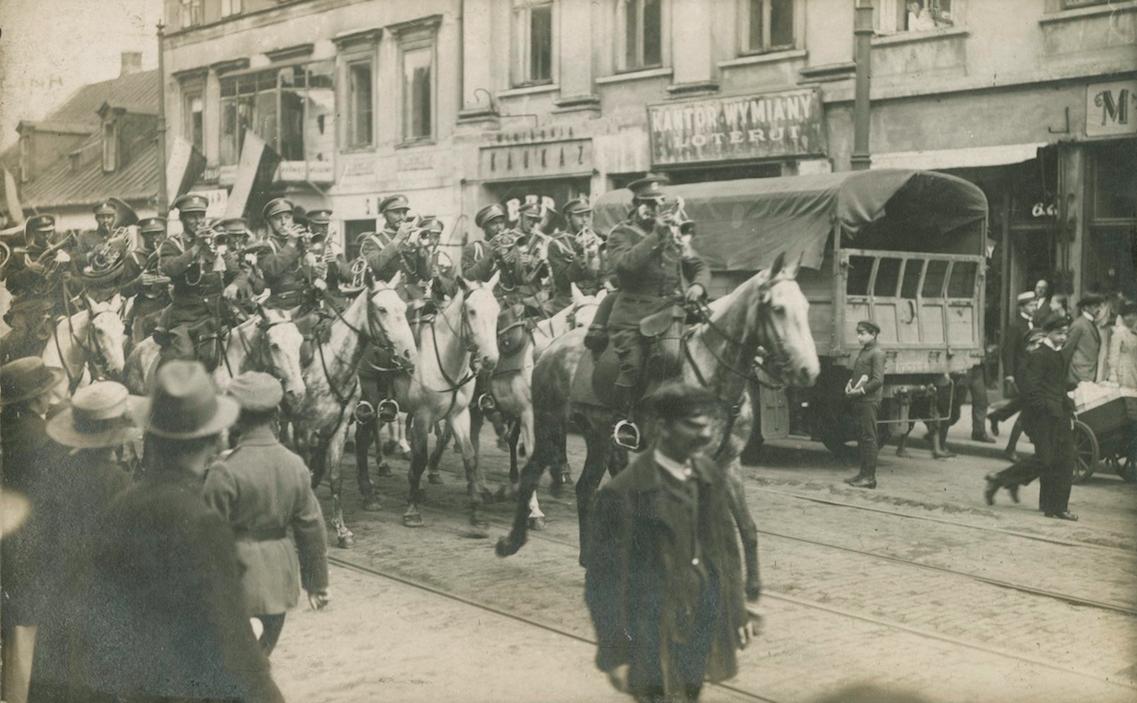 archiwalna ilustracja przedstawiająca konny oddział wojska i obserwującą ich grupę ludzi